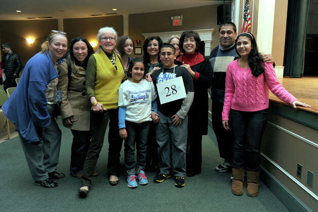 Abram Mikhaeel Goda, 12, of Bridgeport, winner of the Hearst Media Services Regional Spelling Bee, is surrounded by family and friends Thursday night, March 14, 2013. Photo: Carol Kaliff / The News-Times