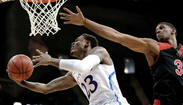 Kansas guard Ben McLemore (23) gets past Texas Tech forward Jordan Tolbert to put up a shot during the second half an NCAA college basketball game in the Big 12 men's tournament Thursday, March 14, 2013, in Kansas City, Mo. Kansas won 91-63. (AP Photo/Charlie Riedel) Photo: Charlie Riedel, Associated Press / AP