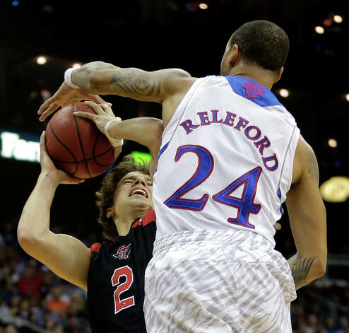Kansas guard Travis Releford (24) blocks a shot by Texas Tech guard Dusty Hannahs (2) during the first half an NCAA college basketball game in the Big 12 men's tournament Thursday, March 14, 2013, in Kansas City, Mo. (AP Photo/Charlie Riedel) Photo: Charlie Riedel, Associated Press / AP