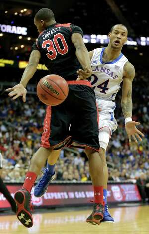 Kansas guard Travis Releford (24) passes the ball around Texas Tech forward Jaye Crockett (30) during the second half an NCAA college basketball game against Texas Tech in the Big 12 men's tournament on Thursday, March 14, 2013, in Kansas City, Mo. (AP Photo/Charlie Riedel) Photo: Charlie Riedel, Associated Press / AP