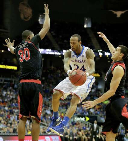 Kansas guard Travis Releford (24) passes the ball between Texas Tech forwards Jaye Crockett (30) and Dejan Kravic (11) during the second half an NCAA college basketball game against Texas Tech in the Big 12 men's tournament Thursday, March 14, 2013, in Kansas City, Mo. (AP Photo/Charlie Riedel) Photo: Charlie Riedel, Associated Press / AP