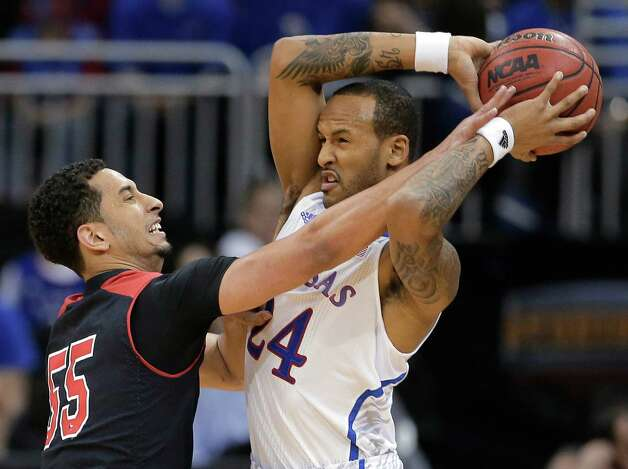 Texas Tech guard Ty Nurse (55) tries to steal the ball from Kansas guard Travis Releford (24) during the first half an NCAA college basketball game in the Big 12 men's tournament Thursday, March 14, 2013, in Kansas City, Mo. (AP Photo/Charlie Riedel) Photo: Charlie Riedel, Associated Press / AP