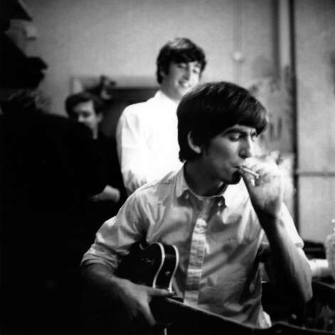George Harrison from The Beatles smokes a cigarette backstage with John Lennon behind at the Finsbury Park Astoria, London during the band's Christmas Show residency in December 1963. Photo: Val Wilmer, Getty Images / Redferns
