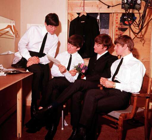 The Beatles read a letter in their dressing room. Photo: Popperfoto, Getty Images / popperfoto.com
