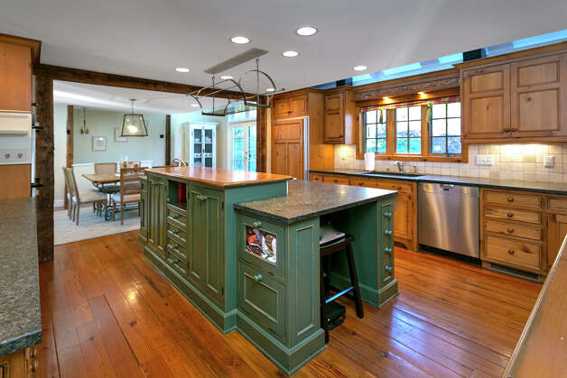 The kitchen features a center island with a wood and granite counter and prep sink, an eat-in area or breakfast room, a large stainless sink and a breakfast bar. Appliances include a Viking six-burner range top and a Miele dishwasher. Photo: Contributed Photo