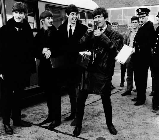The Beatles about to climb onto a bus at London Airport, George Harrison capturing the moment on film with a cine-camera. Photo: Evening Standard, Getty Images / Hulton Archive