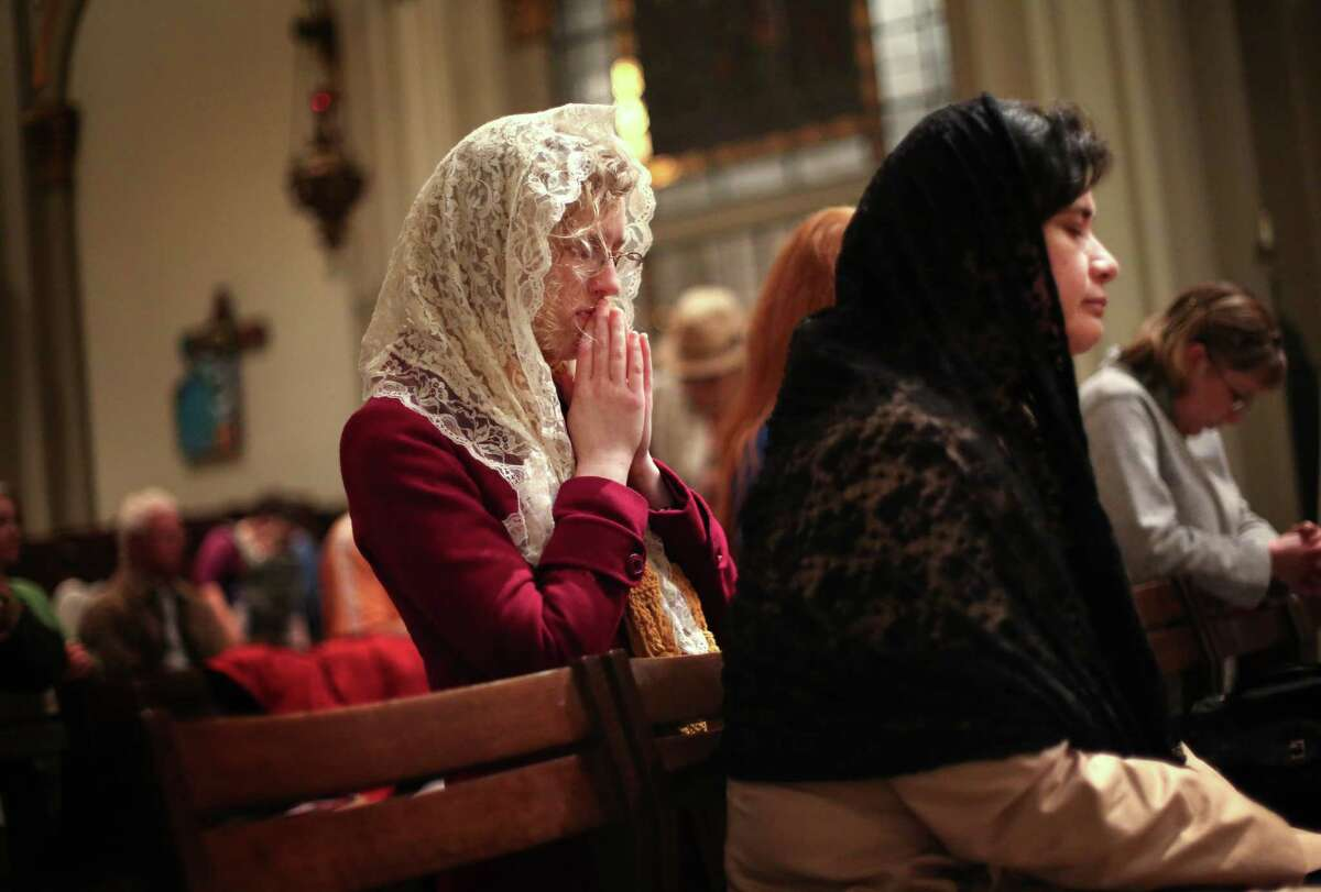 Alane Howard, center left, prays with other faithful during a mass for the new Pope, Francis I, on Wednesday, March 13, 2013 at St. James Cathedral in Seattle. Archbishop of Seattle Peter Sartain held a mass for the new pontiff.