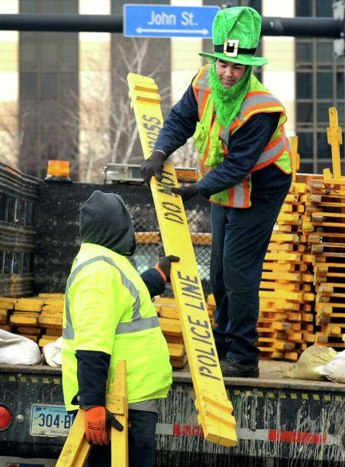 Dressed as a leprechaun, public works employee Steven Lukak helps set up street barricades on Lafayette Blvd. in Bridgeport, Conn. in preparation for the St. Patrick's Day parade today, Friday March, 15, 2013. Photo: Cathy Zuraw / Connecticut Post