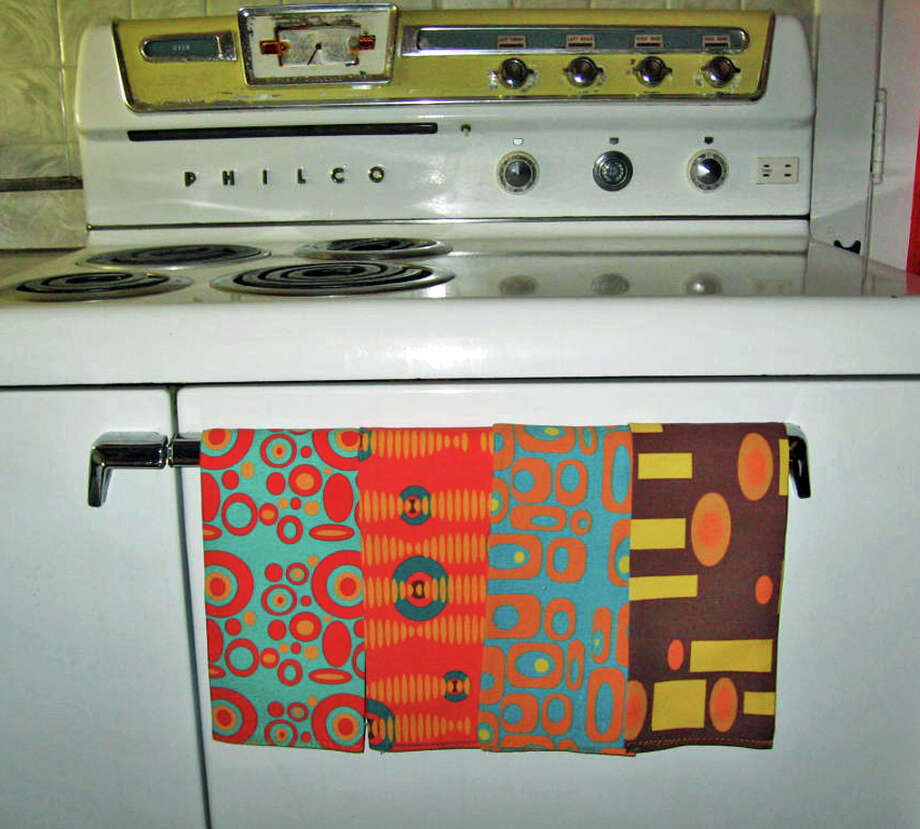 Renee Pedro's custom tea towels rest on the handle of her vintage stove. Pedro has started a business making household goods with fabrics she designs and orders through the Internet. Photo: Courtesy Renee Pedro, HONS / Crash Pad Designs