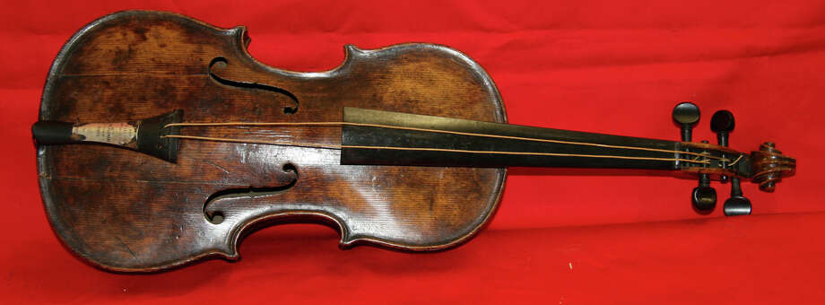 In this undated photo provided by Henry Aldridge on Friday, March 15, 2013 shows the violin that was played by the bandmaster of the Titanic as the oceanliner sank, Devizes, England. Survivors of the Titanic have said they remember the band, led by Wallace Hartley, playing on deck even as passengers boarded lifeboats after the ship hit an iceberg. Hartley's violin was believed lost in the 1912 disaster, but auctioneers Henry Aldridge & Son say an instrument unearthed in 2006 has undergone rigorous testing and proven to be Hartley's. The auction house said has spent the past seven years and thousands of pounds determining the water-stained violin's origins, consulting numerous experts including government forensic scientists and Oxford University. (AP Photo/Henry Aldridge)