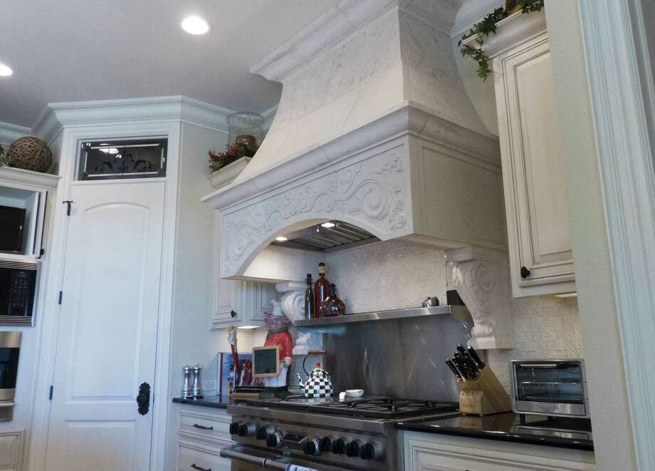 The stone hood is a focal point in the kitchen, but hanging the heavy piece was a challenge.