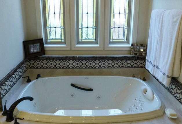 The master bathroom in the home includes stained glass windows over the tub.