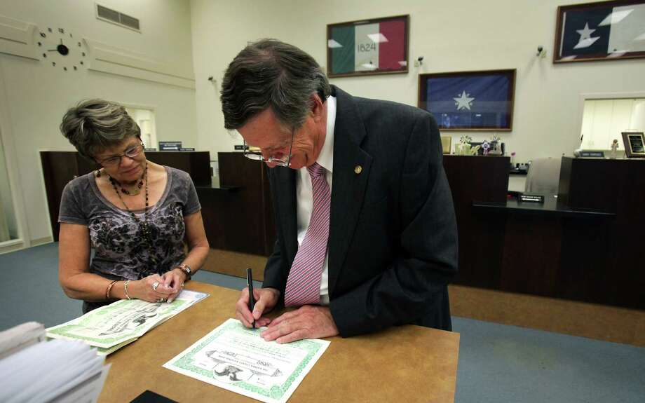 "Hugh B. ""Trip"" Ruckman III, right, chairman, president and CEO of Karnes County National Bank, signs a document for Kathy Spillar, Assistant Vice President of the bank, in the Karnes City bank. Friday, May 25, 2012. Photo: BOB OWEN, San Antonio Express-News / © 2012 San Antonio Express-News"