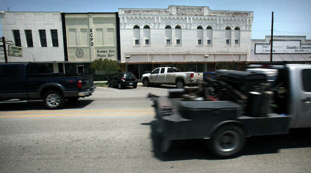 Drilling work trucks pass by historic buildings in downtown Karnes City. Friday, May 25, 2012. Photo: BOB OWEN, San Antonio Express-News / © 2012 San Antonio Express-News