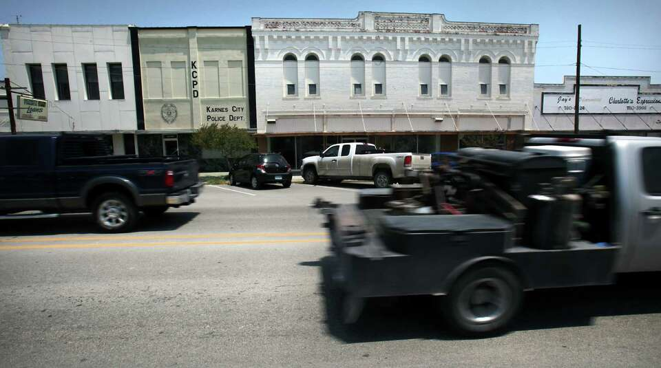 Drilling work trucks pass by historic buildings in downtown Karnes City. Friday, May 25, 2012.