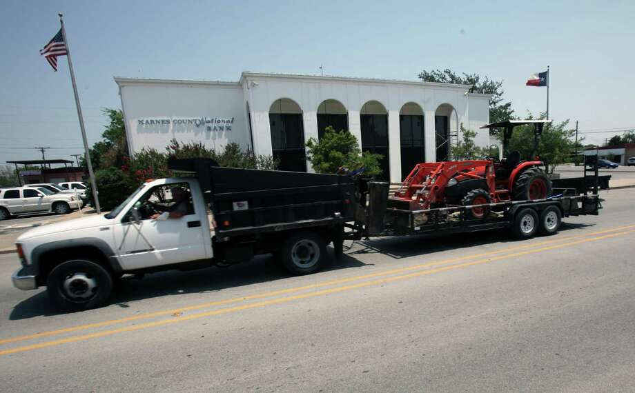 A work truck whizzes by the Karnes County National Bank on Friday, May 25, 2012. Photo: BOB OWEN, San Antonio Express-News / © 2012 San Antonio Express-News