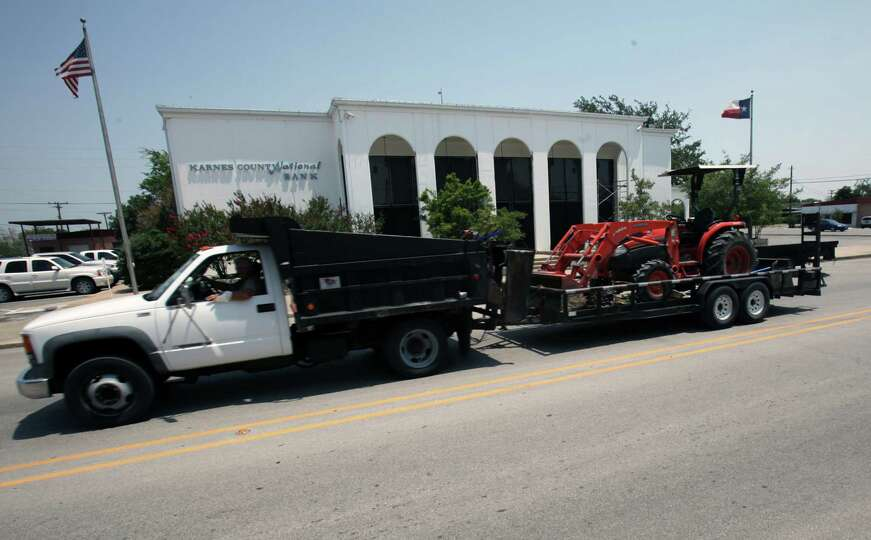 A work truck whizzes by the Karnes County National Bank on Friday, May 25, 2012.