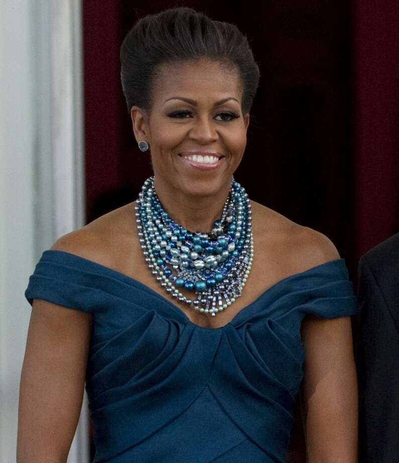 An updo and a sparkling necklace complement a Marchesa gown as the first lady awaits the arrival of British Prime Minister David Cameron prior to a State Dinner at White House in 2012.