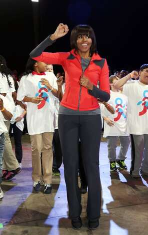 Michelle Obama dances with school children during a debut of a school exercise program February 28, 2013, in Chicago, Ill.