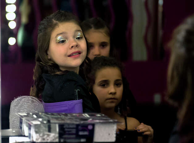 "As her friends look on 11 year-old Saide Heiner (left) looks into the mirror after having some eye glitter applied during her ""glamour girl"" birthday party at Sharkey's Cuts for Kids March 10, 2013. Photo: Steve Faulisi, San Antonio Express-News / ? 2013 San Antonio Express-News"
