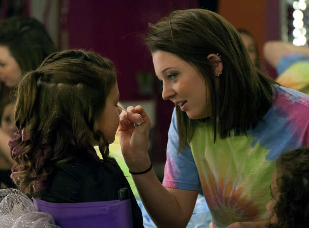 "11 year-old Saide Heiner (left) has some make-up applied by stylist Ashta Ermis (right) as one of friends looks one during her ""glamour girl"" birthday party at Sharkey's Cuts for Kids March 10, 2013. Photo: Steve Faulisi, San Antonio Express-News / ? 2013 San Antonio Express-News"