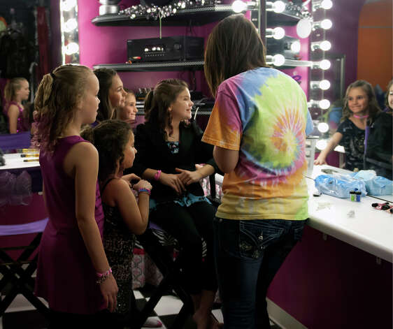 "As her friends look on 11 year-old Saide Heiner (middle) looks into the mirror after stylist Ashta Ermis (right) finished applying some make-up during her ""glamour girl"" birthday party at Sharkey's Cuts for Kids March 10, 2013 Photo: Steve Faulisi, San Antonio Express-News / ? 2013 San Antonio Express-News"