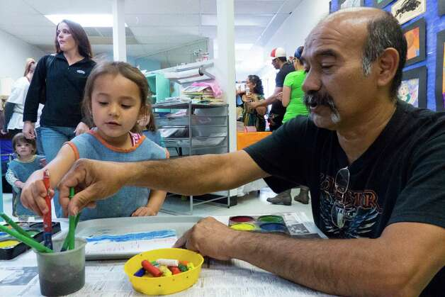 Eddie Frias and his daughter, Bryanna, participate in a birthday party at Artworks Art Studio on Saturday, March, 9, 2013. Photo: Billy Calzada, San Antonio Express-News / San Antonio Express-News