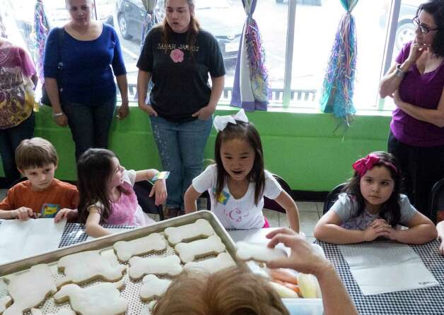 Liliana Jin Gomez, 7, middle, watches as cookies are passed out to be decorated with frosting during her birthday party at Cookie Party Time on Saturday, March 9, 2013. Photo: Billy Calzada, San Antonio Express-News / San Antonio Express-News