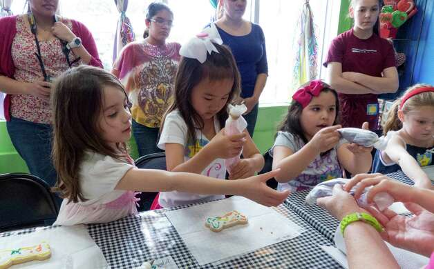 Genna Dieges, left, and birthday girl Liliana Jin Gomez, 7, join other friends in a birthday party at Cookie Party Time on Saturday, March 9, 2013. Photo: Billy Calzada, San Antonio Express-News / San Antonio Express-News
