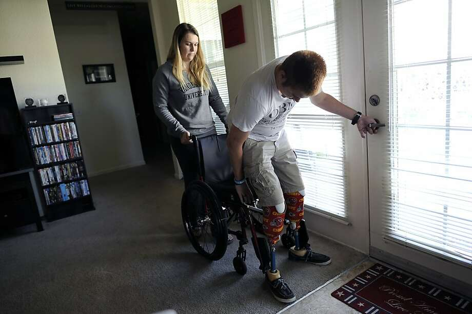 Jennifer Jergens helps her husband, Brian, into his wheelchair. Brian lost both legs and suffered a brain injury in Afghanistan. Photo: Michael Short, Special To The Chronicle