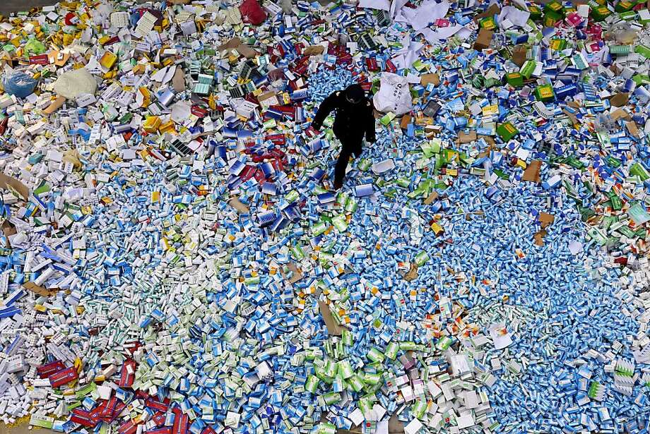 This picture taken on March 14 shows a Chinese policeman walking across a pile of fake medicines seized in Beijing in recent months, which were later destroyed.  The rapid growth of Internet commerce has led to an explosion of counterfeit drugs sold around the world, with China the biggest source of fake medicines, pharmaceutical experts said as the illicit trade is now believed to be worth around 75 billion USD globally, with criminal gangs increasingly using the web to move their products across borders. Photo: Str, AFP/Getty Images