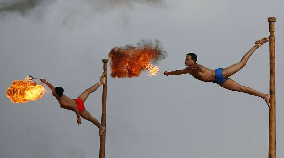 The earmarks of a good officer:As if tying one's foot to the top of a steep pole isn't enough, Indian army soldiers must also spit fire when they perform the mallakhamb, a traditional gymnastic sport, during a skills display at Officers Training Academy in Chennai. Photo: Arun Sankar K, Associated Press