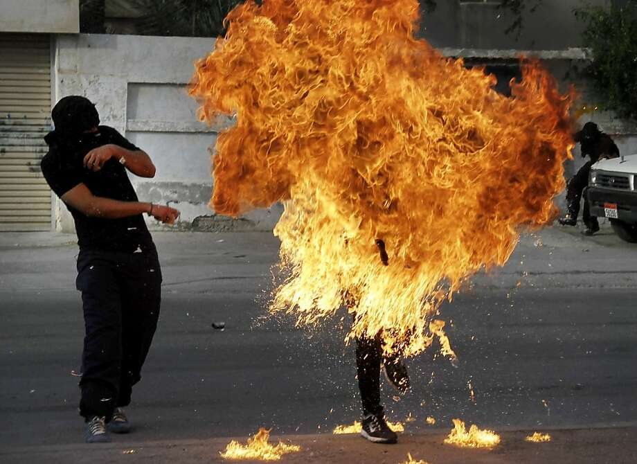 Flames engulf a Bahraini anti-government protester after a shot fired by riot police hit a gasoline bomb he was preparing to throw during clashes in Sanabis. His condition was not known. Photo: Hasan Jamali, Associated Press