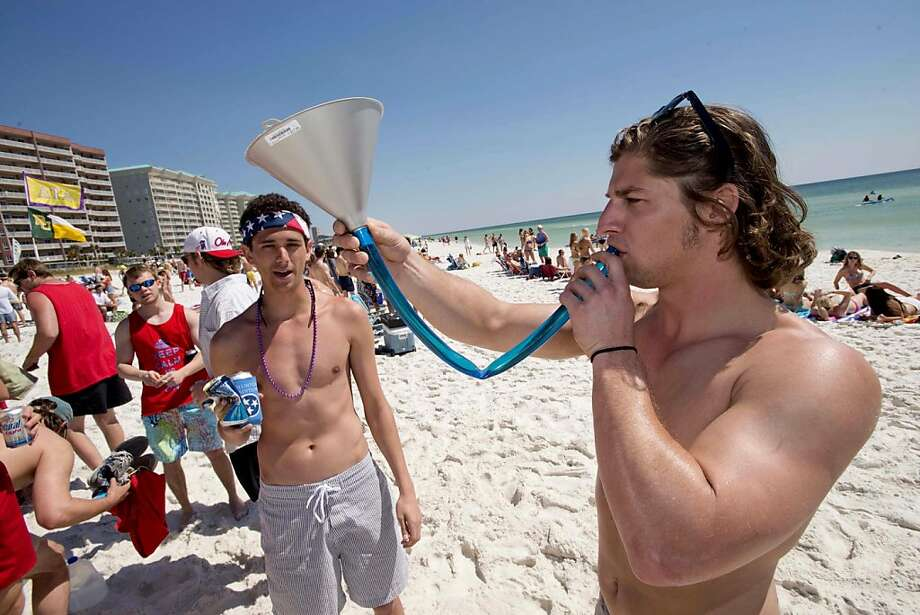 Running about a quart low, Drew Moyes rehydrates with a brewed beverage on the beach in South Walton County, Fla. Being over 21, Moyes is legally entitled to drink alcohol through an oil funnel. Photo: Devon Ravine, Associated Press