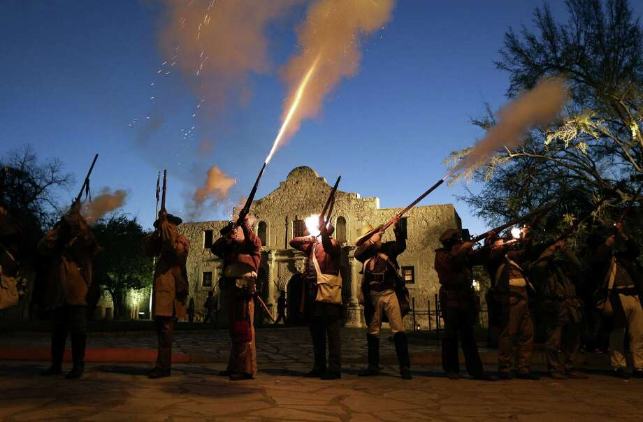 Members of the San Antonio Living History Association fire muskets in a recent ceremony to remember the 1836 Battle of the Alamo. Our readers comment on the origins of the battle and the bravery of the men who fought there. Photo: Eric Gay / Associated Press