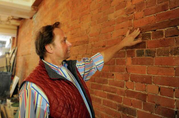 Clyde Ripka touches the exposed brick in the 7,000 square foot space which will house Ripka's Bridgeport Market, opening in May. The full-service grocery store and café will be located within the Arcade building on Main Street in downtown Bridgeport, Conn. Photo: Autumn Driscoll / Connecticut Post