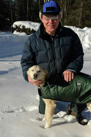 Stan Smith of Birchwood, Alaska, is taking care of Newton Marshall's Iditarod sled dog on Thursday,