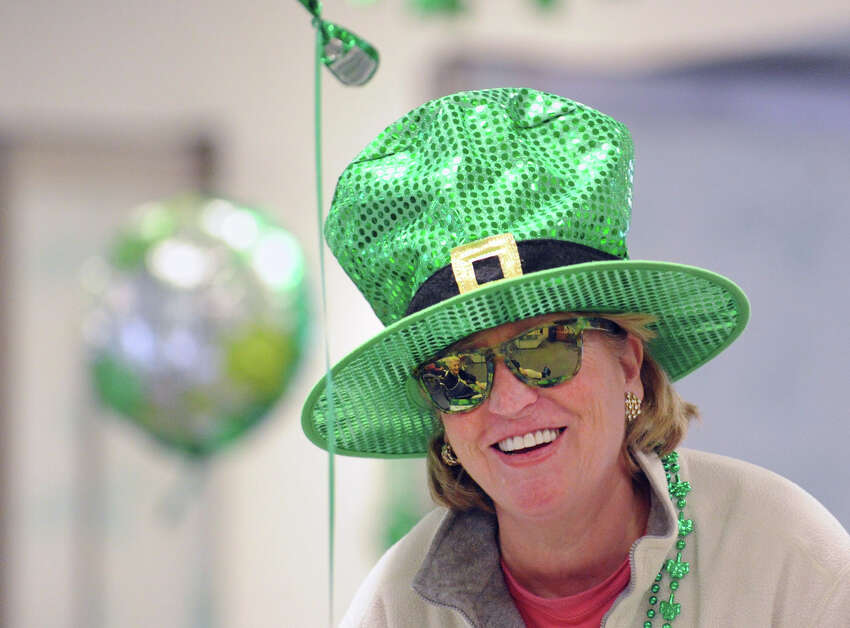 Mary Bruce, coordinator of recreation services for Nathaniel Witherell, smiles while wearing a green hat and green sunglasses during the annual St. Patrick's party at the facility in Greenwich, Friday, March 15, 2013.