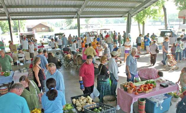 Early morning shoppers browse a wide variety of offerings including produce, fresh eggs, honey and baked goods at Beaumont Farmers Market held Saturdays at the College Street Athletic Complex. Photo: Amos Morale