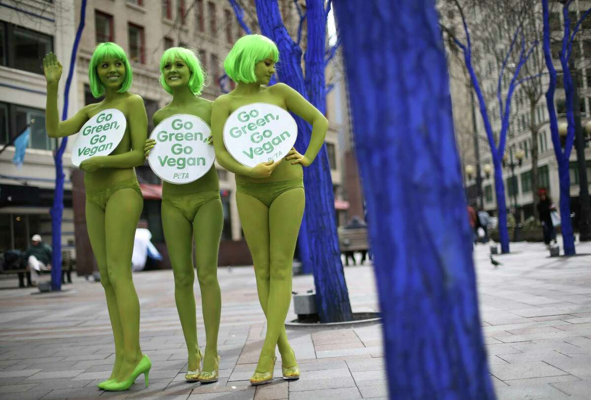 PETA activists Emily Lavender, Julia De Courcy and Tohni Blower shed their clothes for bright green paint at Seattle's Westlake Park on Friday, March 15, 2013. The trio were using the action to bring attention to their advocacy for a vegan diet.