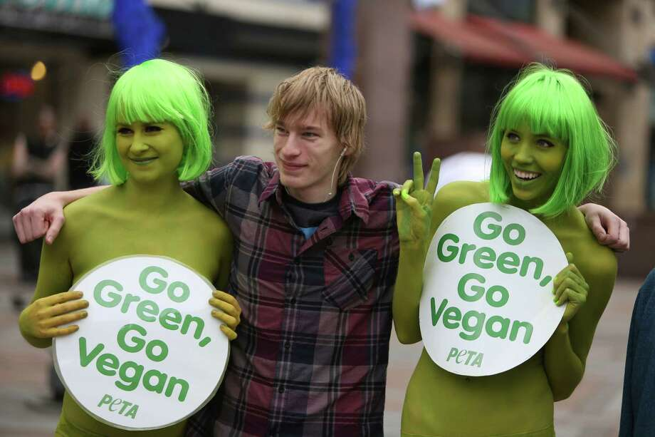 PETA activists Tohni Blower and Emily Lavender pose with a passerby  at Seattle's Westlake Park on Friday, March 15, 2013. The trio were using the action to bring attention to their advocacy for a vegan diet. Photo: JOSHUA TRUJILLO / SEATTLEPI.COM