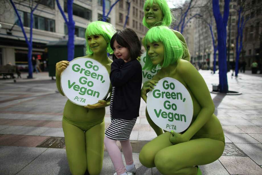 PETA activists Tohni Blower, Julia De Courcy and Emily Lavender pose for a photo with Mikaela Torres at Seattle's Westlake Park on Friday, March 15, 2013. The trio were using the action to bring attention to their advocacy for a vegan diet. Photo: JOSHUA TRUJILLO / SEATTLEPI.COM