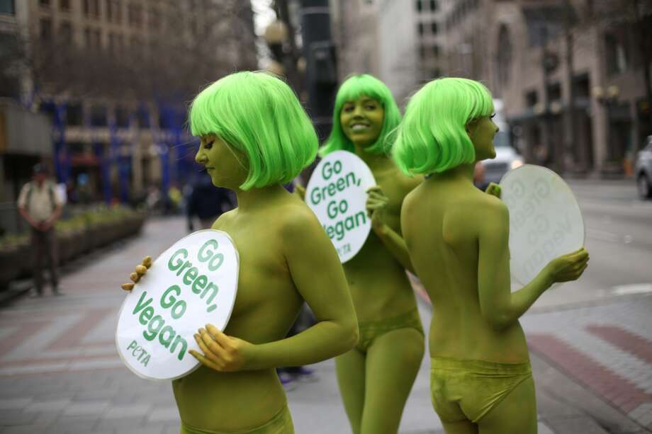 PETA activists, from left, Tohni Blower, Emily Lavender and Julia De Courcy shed their clothes for bright green paint at Seattle's Westlake Park on Friday, March 15, 2013. The trio were using the action to bring attention to their advocacy for a vegan diet. (Joshua Trujillo, seattlepi.com)