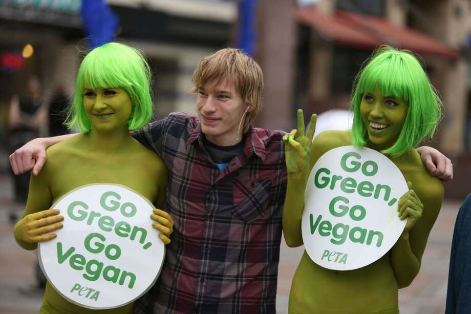 PETA activists Tohni Blower and Emily Lavender pose with a passerby  at Seattle's Westlake Park on Friday, March 15, 2013. The trio were using the action to bring attention to their advocacy for a vegan diet. (Joshua Trujillo, seattlepi.com)
