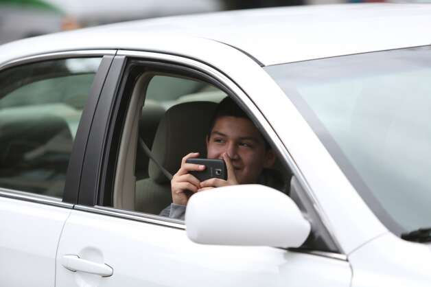 A passenger in a car takes a photo of PETA activists after they shed their clothes for bright green paint at Seattle's Westlake Park on Friday, March 15, 2013. The trio were using the action to bring attention to their advocacy for a vegan diet. (Joshua Trujillo, seattlepi.com)