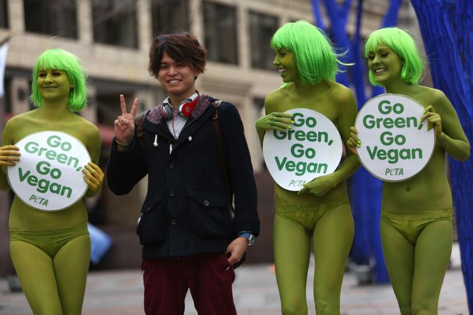 PETA activists Tohni Blower Emily Lavender and Julia De Courcy pose with a passerby at Seattle's Westlake Park on Friday, March 15, 2013. The trio were using the action to bring attention to their advocacy for a vegan diet. (Joshua Trujillo, seattlepi.com)