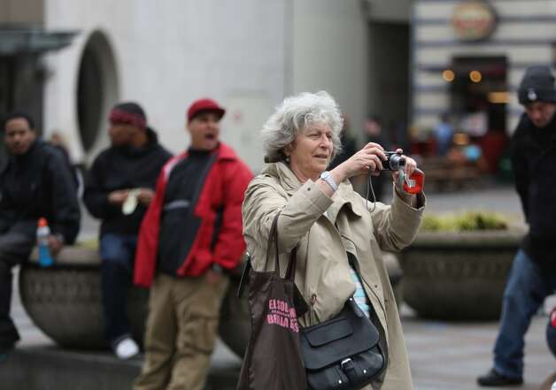 A woman stops to take a photo as PETA activists Emily Lavender, Julia De Courcy and Tohni Blower shed their clothes for bright green paint at Seattle's Westlake Park on Friday, March 15, 2013. The trio were using the action to bring attention to their advocacy for a vegan diet. (Joshua Trujillo, seattlepi.com)