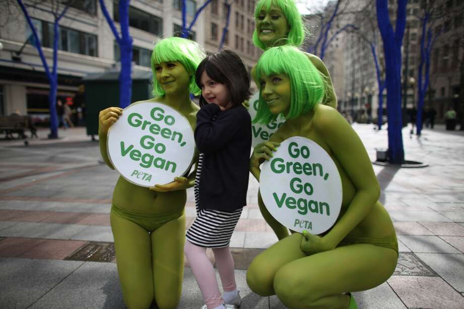 PETA activists Tohni Blower, Julia De Courcy and Emily Lavender pose for a photo with Mikaela Torres at Seattle's Westlake Park on Friday, March 15, 2013. The trio were using the action to bring attention to their advocacy for a vegan diet. (Joshua Trujillo, seattlepi.com)