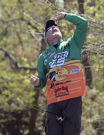 Angler Dennis Tietje jokes around by acting like he is going to eat a small bass on the second day of the 2013 Bassmasters Elite Series Sabine River Challenge. Photo taken: Randy Edwards/The Enterprise