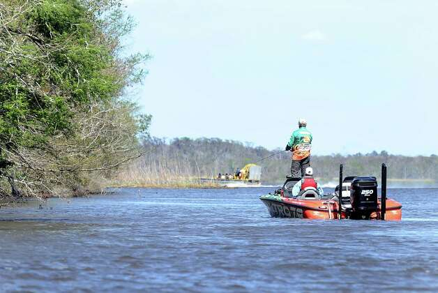 Angler Dennis Tietje works the bank near the boat ramp as a air boat blasts by on the second day of the 2013 Bassmasters Elite Series Sabine River Challenge. Photo taken: Randy Edwards/The Enterprise